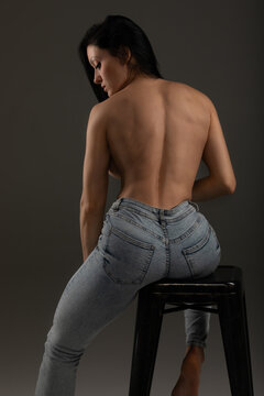 Attractive brunette in blue jeans against grey wall.