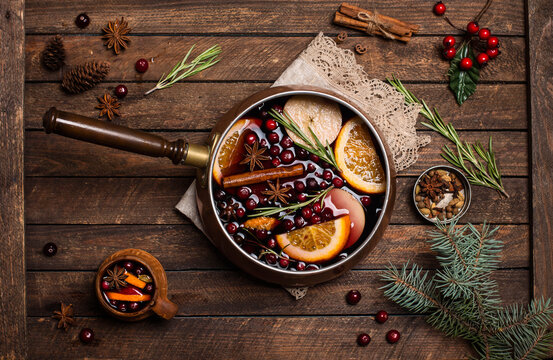 Christmas mulled red wine with the addition of spices and citrus fruits in a small vintage copper pan on a rustic wooden table, top view. Pot of mulled wine, traditional christmas drink.