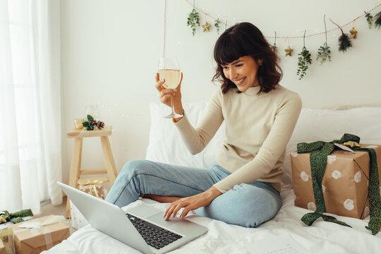 Woman celebrating christmas on video call raising wine glass