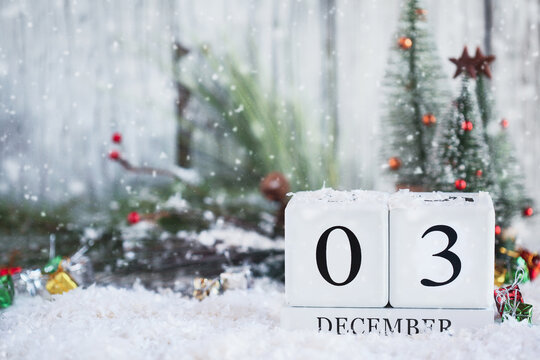 Giving Tuesday or National Disability Day. White wood calendar blocks with the date December 3rd and Christmas decorations with snow. Selective focus with blurred background.