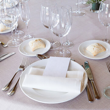 Detail of a beautiful wedding table with crockery, cutlery and wine glasses with a blank menu paper for mock up