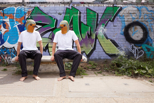 Two men in latex bird masks talk to each other on a seat in front of a graffitied wall.  It is urban.