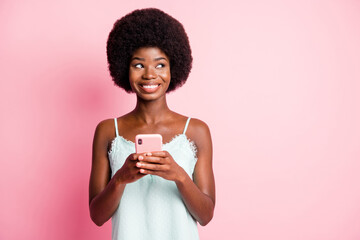 Photo of brown curly haired pretty young woman look copyspace think comment hold phone wear singlet isolated on pink color background Wall mural