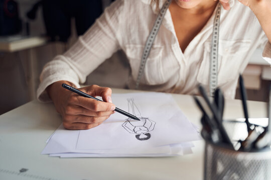 Couturier using pencil for modeling sketches