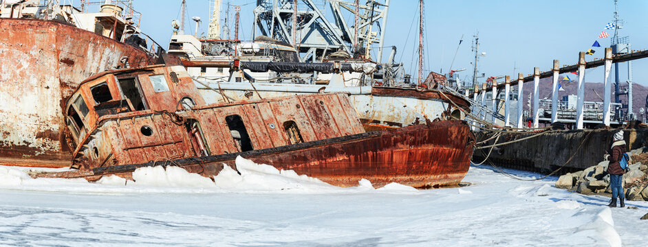 Old abandoned ship in the Sea of Japan. Rusty ship, frozen in the ice on the coast. Background with abandoned rusty ship for photoshop and design. Small overturned rusty broken fishing ship
