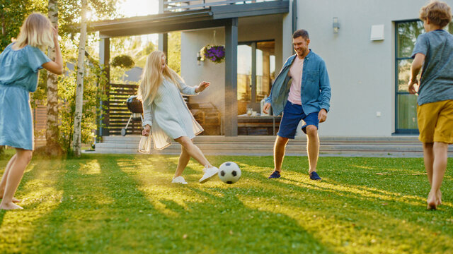 Happy Family of Four Playing Soccer, Passing Football to Each Other. Mother, Father, Daughter and Son Have Fun Playing Games in the Backyard Lawn of Idyllic Suburban House on Sunny Summer Day