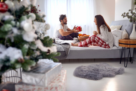 young beardy guy surprising his girlfriend with Christmas present while having breakfast in bed together