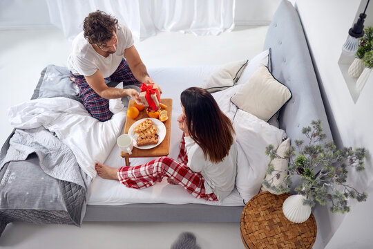 top view of young couple having breakfast in bed. female surprised by wrapped gift from a male