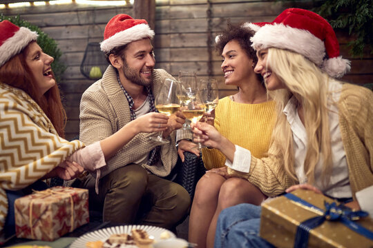 group of friends toasting with sparkling wine and santa clause hats on heads. Christmastime, new year concept