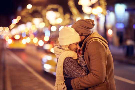 A young couple in love standing in a hug on the street. Relationship, together, Xmas