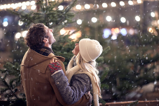 A young couple in hug watching snowflakes in the city. Christmas tree, love, relationship, Xmas, snow