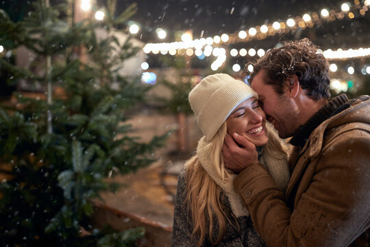 A young couple in love and moments of closeness on a snowy weather in the city. Christmas tree, love, relationship, Xmas, snow