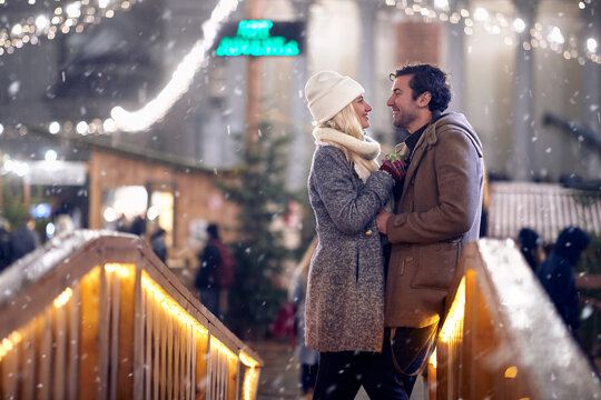 A young couple in love standing on the beautiful bridge at christmas festival on a snowy weather in the city. Festival, love, relationship, Xmas, snow