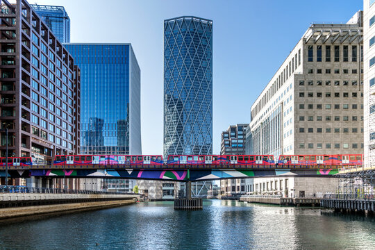Dockland Light Railway (DLR) train crossing Middle Dock at Canary Wharf, Docklands, London