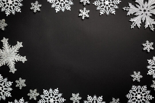 Christmas holidays composition with white christmas decorations and snowflakes on black background with copy space for your text