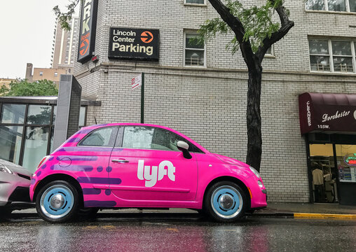 Fiat 500 painted pink and carrying a Lyft logo.