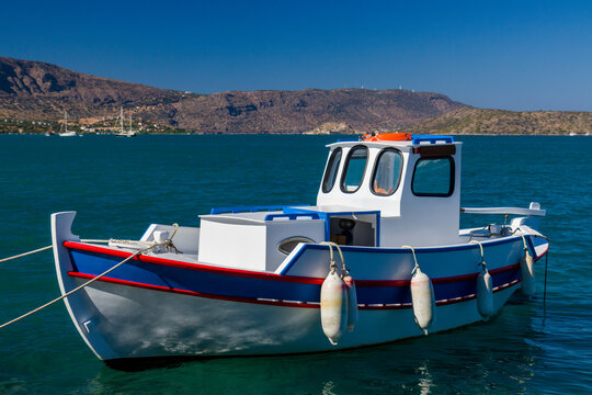 Colorful wooden fishing boat in a small harbour in Greece