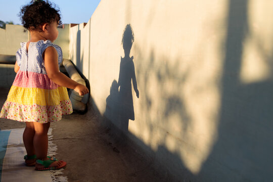Baby girl watches her shadow on the wall in wonder