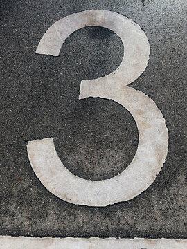 number 3 on asphalt road
