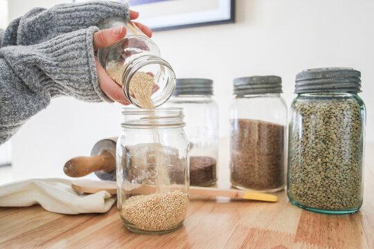 Woman pouring Quinoa into jar