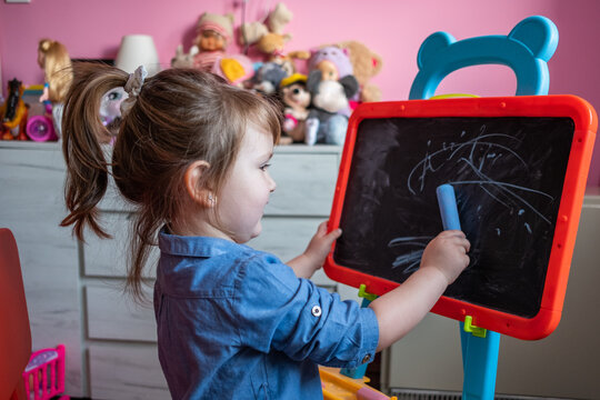 Three-Year-Old Girl Drawing With Chalk On The Blackboard