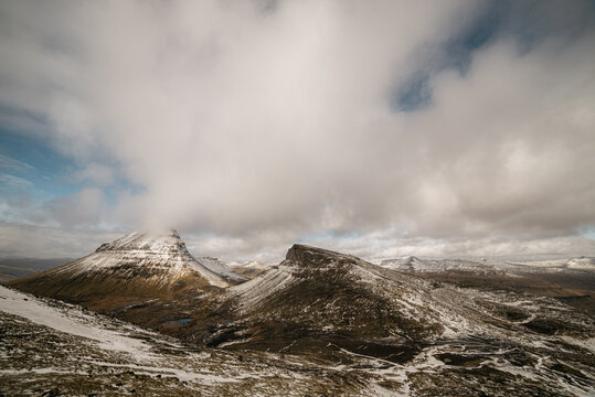 Snowy mountains against cloudy sky