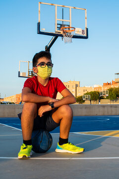 Vertical shot of a boy sitting on a ball wearing a sanitary mask-concept of the new normal