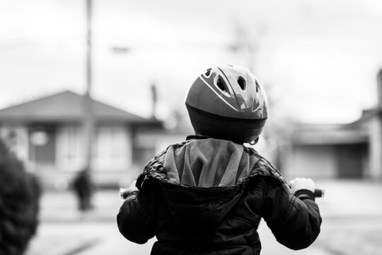 black and white image of a boy sitting on bike