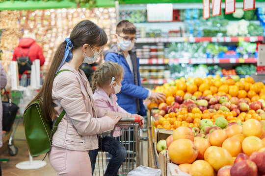Mom with children in protective masks choose fruits to buy in the store