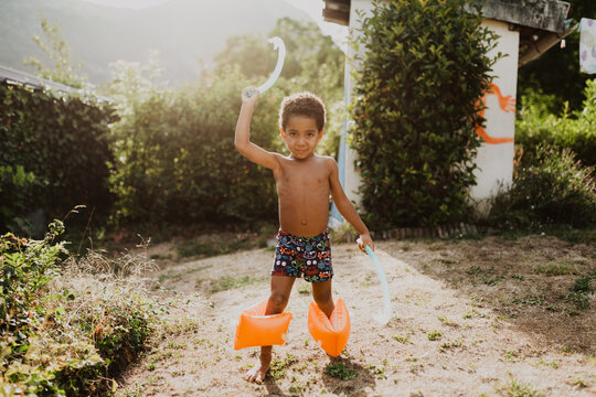 African American boy playing with pool items in a garden