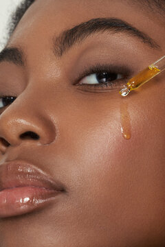 Model with face serum dripping on face