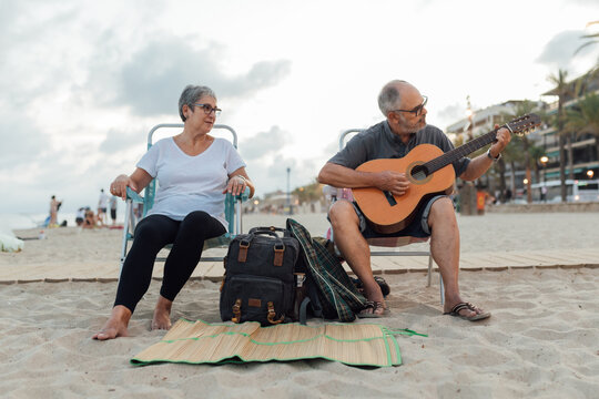 Retired couple playing guitar on a summer afternoon at the beach