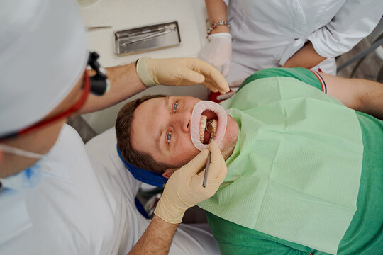 a man is lying in a dentist's chair with his mouth open