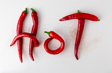 Inscription Hot made of red hot chili peppers on a white background