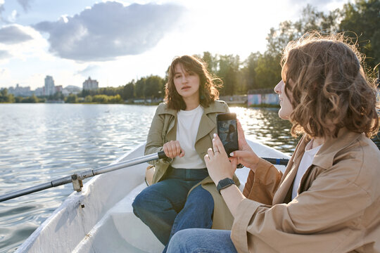 two girls are rowboat on a lake in the Park, taking photos and shooting videos on a smartphone