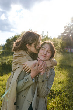 two girls near the river in the city Park. sister hugs and kiss on the cheek