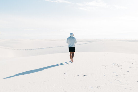 A single man wearing a hoodie walking through a sand filled desert barefoot