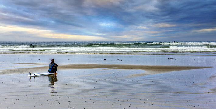 A landscape pic with a surfer sitting on her board looking at the waves