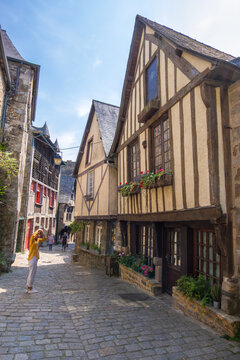 Dinan, France - August 26, 2019: View of historic colombage half-timbered and stone houses on the old cobblestoned street of Dinan, French Brittany