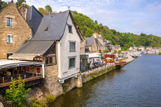 Dinan, France - August 26, 2019: Medieval stone houses with cafes and restaurants in the Dinan Port on the Rance River, French Brittany