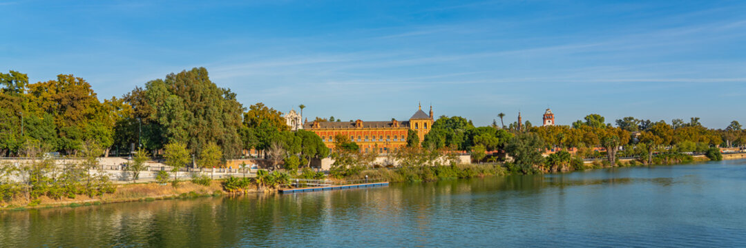 Historical Palacio de San Telmo in Baroque architecture on the green embankment of Guadalquivir river in Seville, panorama