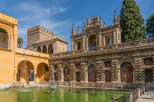 The Fountain with the historical building with painting in the yard of the Real Alcazar Palaces in Seville