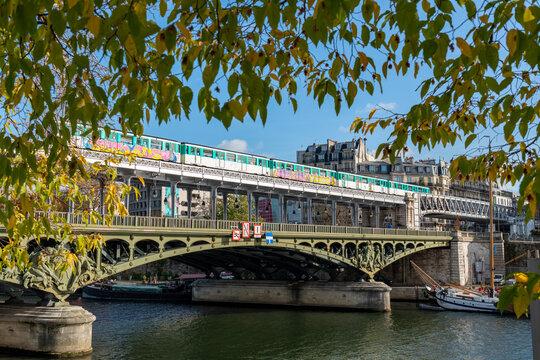 Paris, France - November 13 2020: Metro with graffiti on Pont Bir-Hakeim in Autumn. Shot through the foliage of the Isle of the Swans (Ile aux Cygnes).