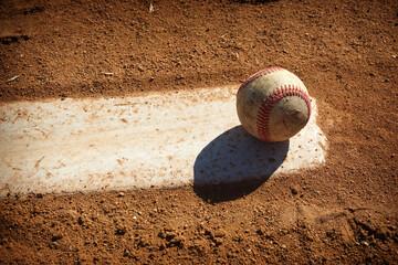 Baseball on pitcher mound of dirt ball field