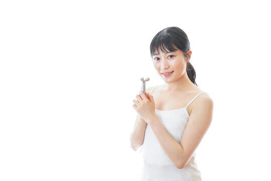 かっさで肌をマッサージをする若い女性