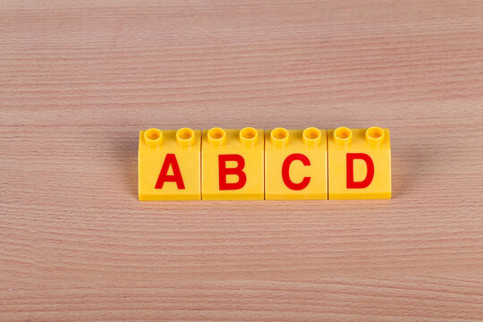 Lego parts with Latin letters on the wooden table