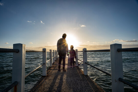 Looking out over a pier against the ocean with a father and son in silhouette, a dusk horizon sky