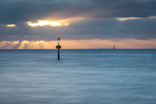 a bay marker against a dusk sky with the ocean in motion