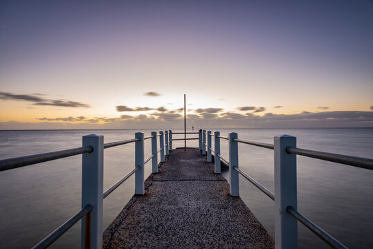 Looking out over a pier against the ocean, a purple dusk horizon sky