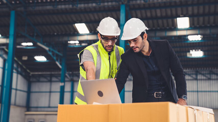 Two factory workers working and discussing manufacturing plan in the factory . Industry and...